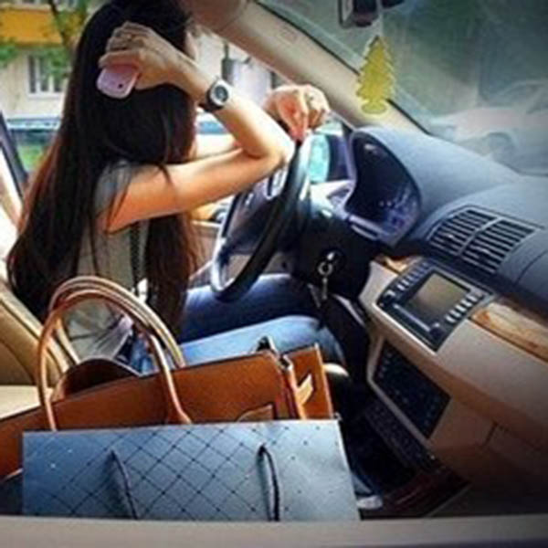 Girl putting elbow on steering of car