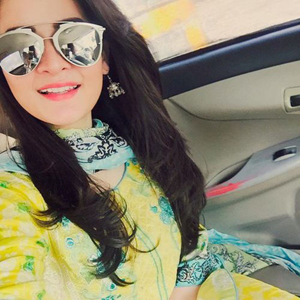 Girl with sunglasses taking selfie in car
